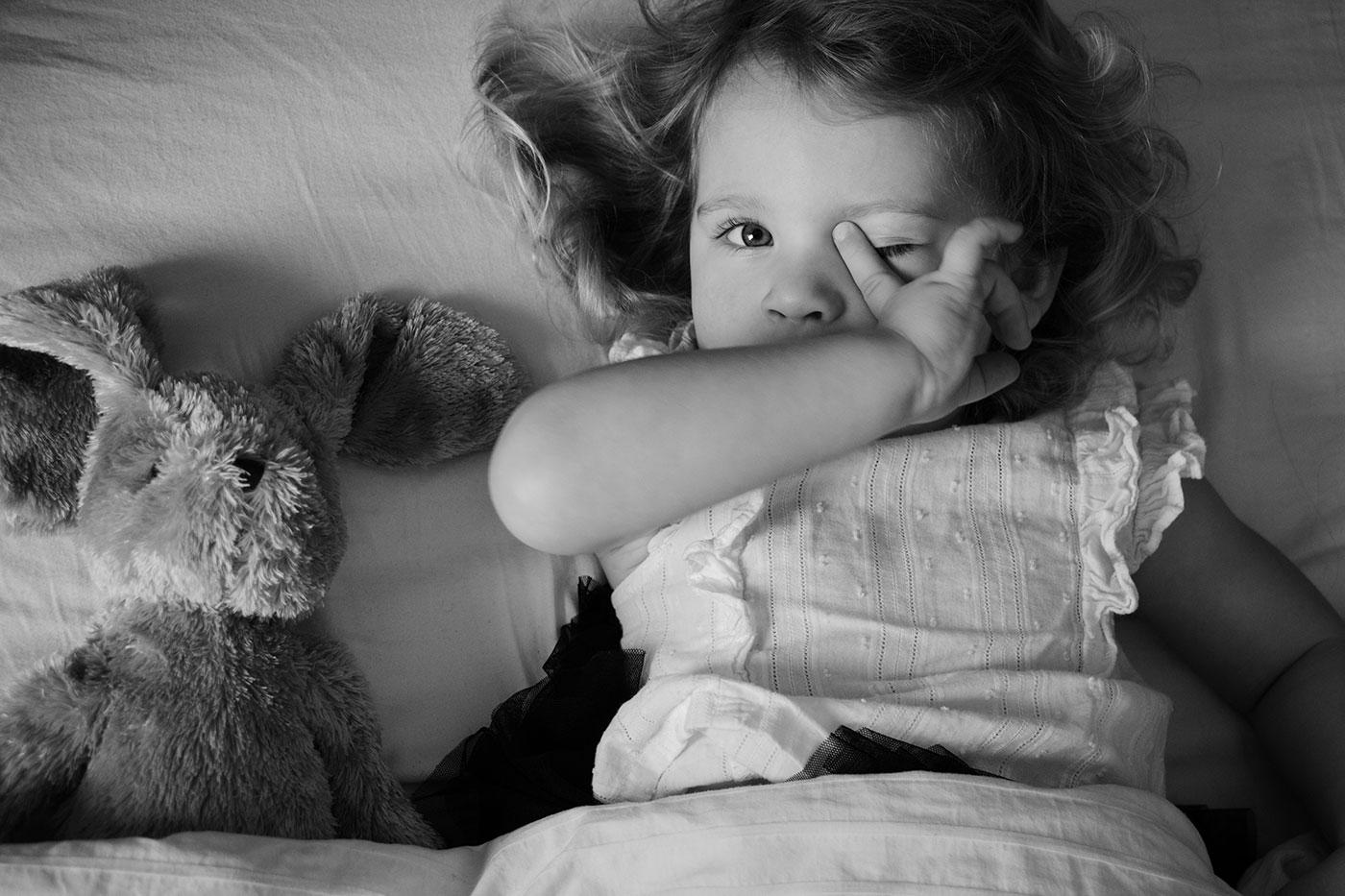 Trött flicka i sängen med sin gosekanin