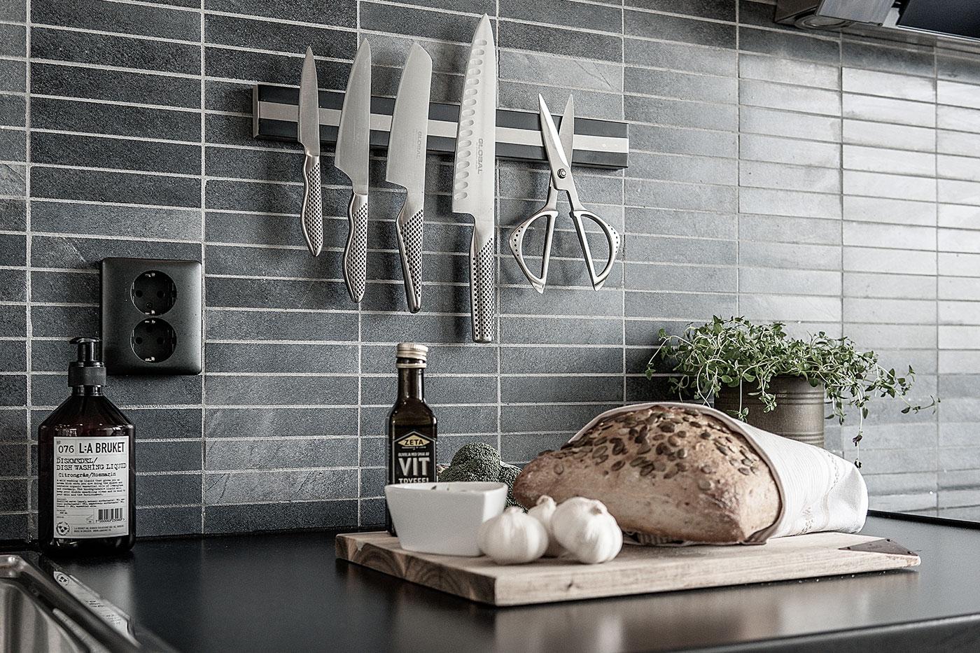 Bröd, vitlök och olja i kök med knivar och sax på väggen