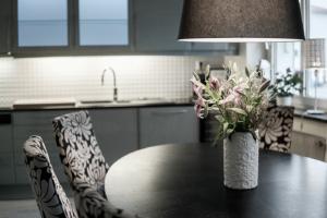 Rosa liljor i vas på bord i kök