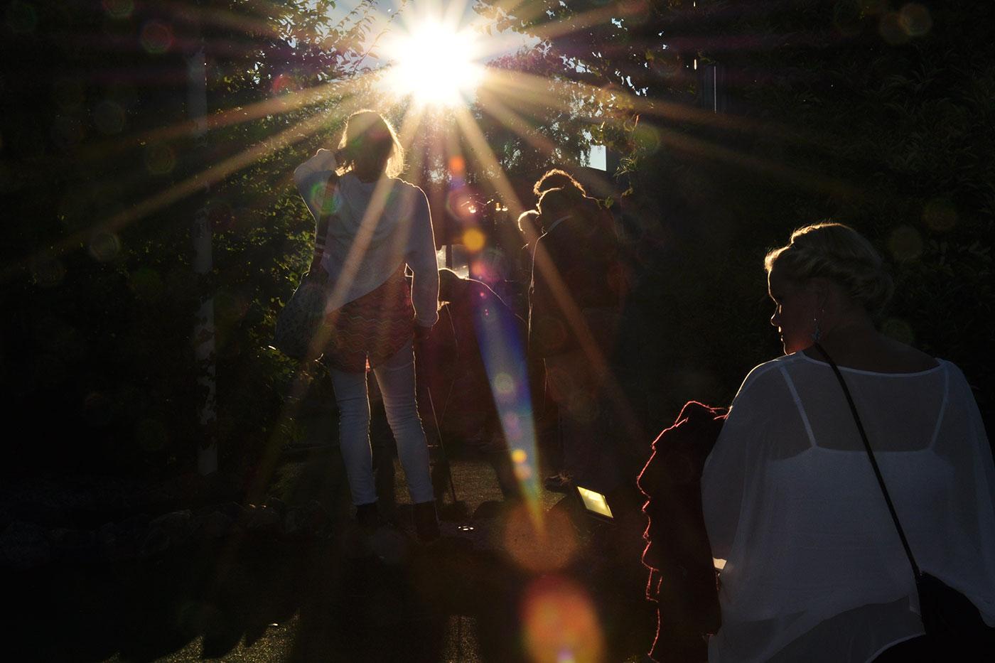 Folk i motljus en sommarkväll i Tylösand