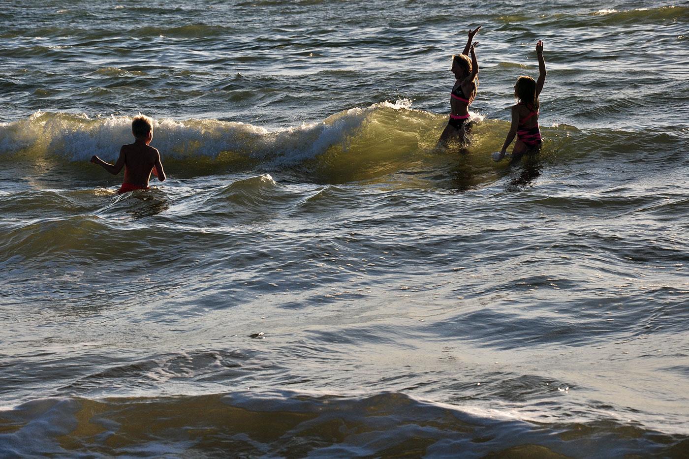 Barn som badar i vågorna Tylösand