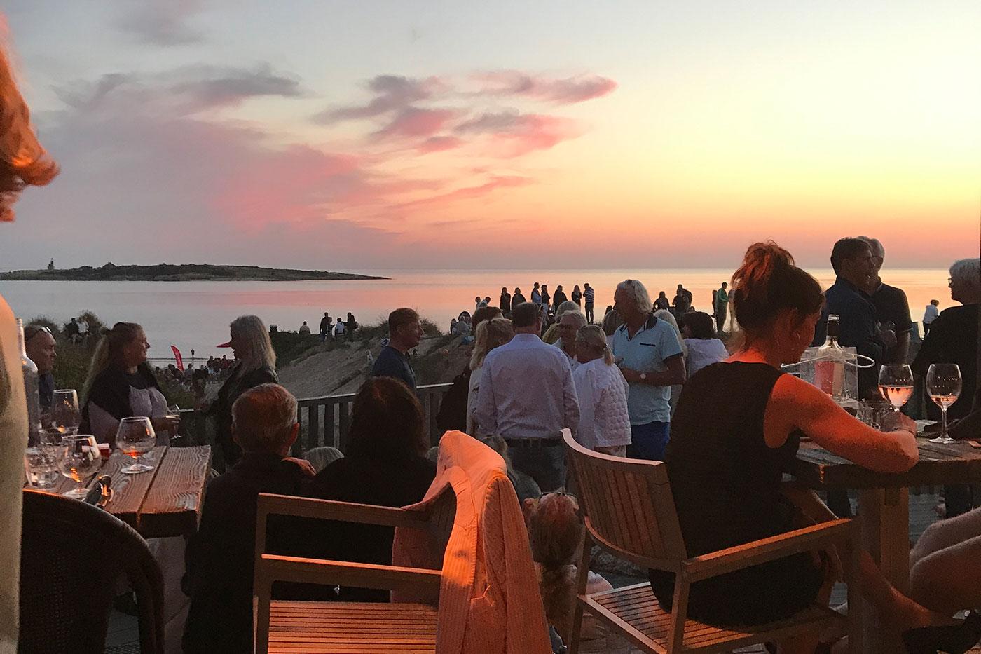 Människor som minglar på Bettans bar i solnedgång Tylösand