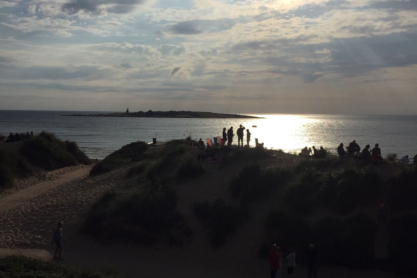 Stranddynor med folk som ser på solnedgång över Tylön Tylösand Halmstad