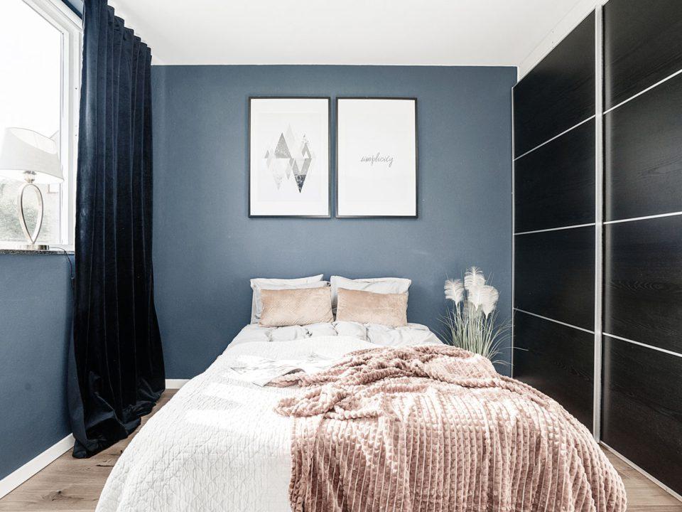 Blått sovrum med svarta skjutdörrar i garderob, aprikos filt