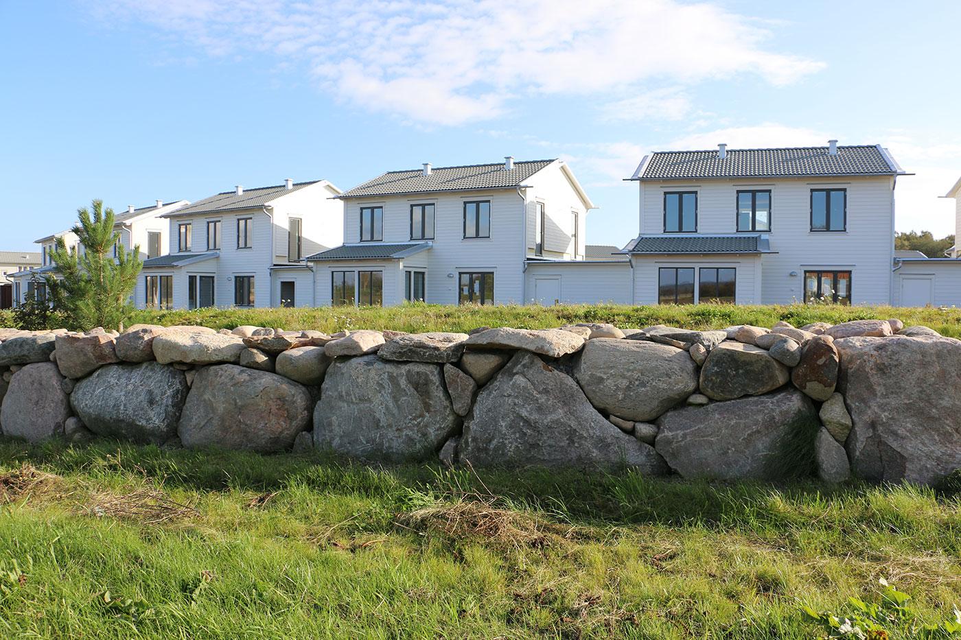 Albinsro - vita hus på rad med stenmur