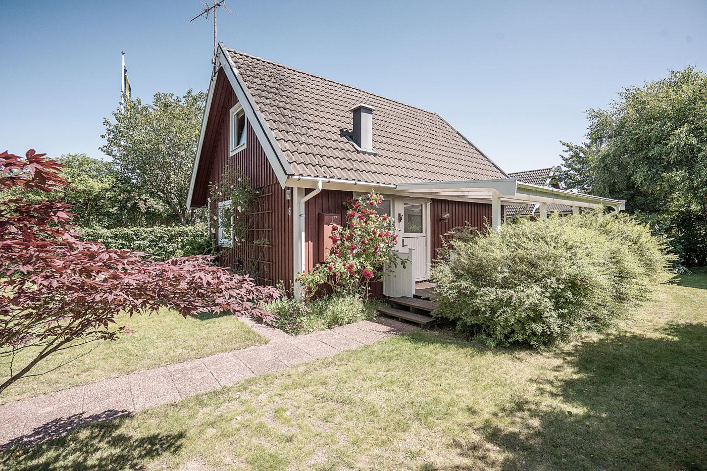 Röd stuga med vita knutar, veranda
